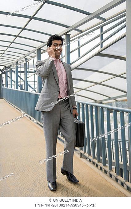 Businessman talking on a mobile phone on a footbridge, Gurgaon, Haryana, India