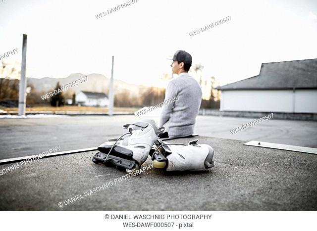 Young man sitting on ramp with inline skates