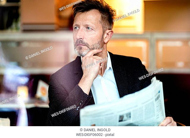 Portrait of pensive mature businessman with newspaper in a coffee shop
