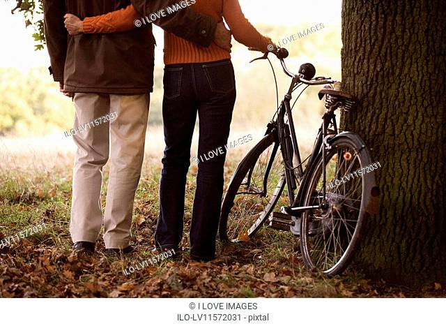 A senior couple standing next to a bicycle, with arms around each other