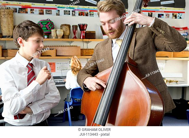 Music teacher guiding middle school student playing double bass in music class