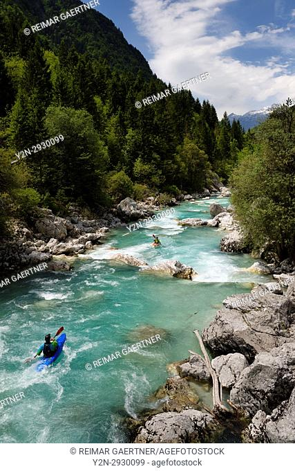 Kayakers shooting the cold emerald green alpine water of the Upper Soca River near Bovec Slovenia with Kanin mountains in the Julian Alps