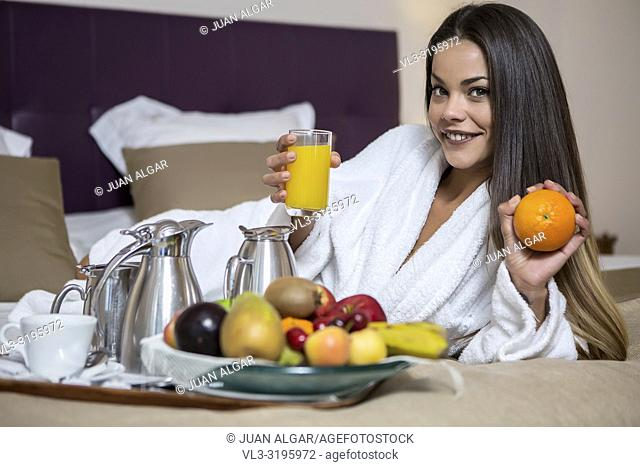Young beautiful woman in hotel morning gown lying on bed with juice and orange with plate full of fresh fruits laid near