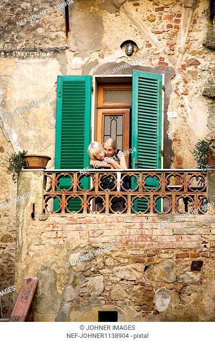 Mother embracing son on balcony of old house