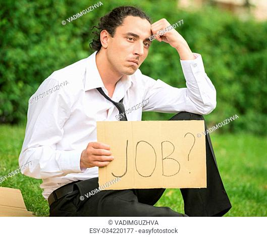 Frustrated unemployed man with sign sitting at the lawn