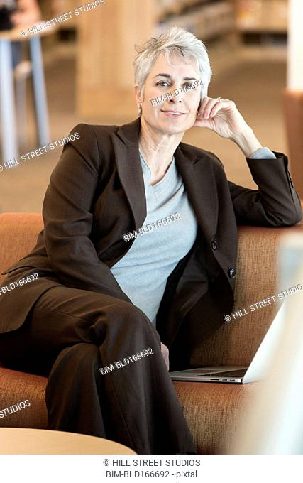 Caucasian businesswoman using laptop on sofa