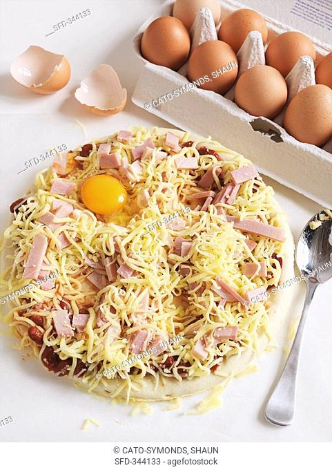 An unbaked pizza topped with ham, cheese and egg