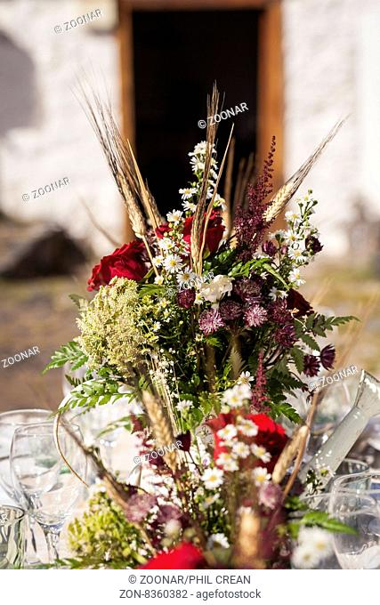 Center piece flowers on a table outdoors set for a celebration
