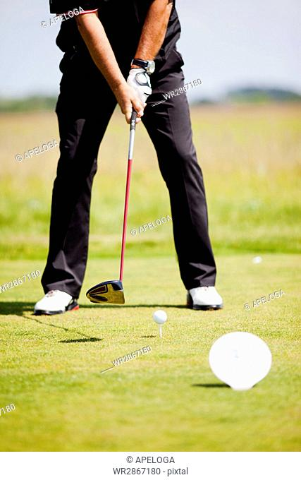 Low section of man playing golf on field