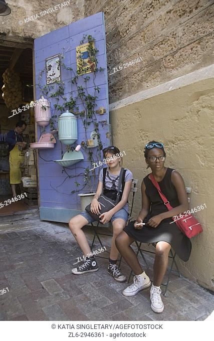Two teenage girls, one African American and one caucasian sitting, tired at the outside of a store front in the Quarter of Le Panier in Marseilles
