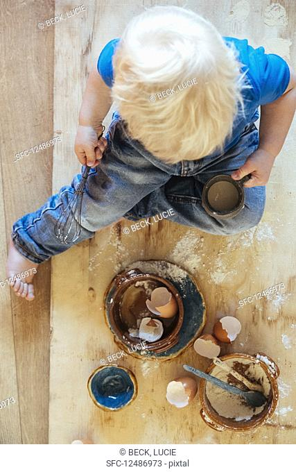 Child helping with cooking. Ingredients eggs, egg shels and flower