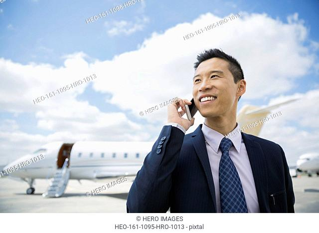 Businessman talking on cell phone on tarmac