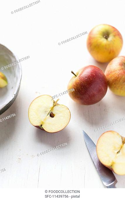 Apples on a white surface with a halved apple and a knife
