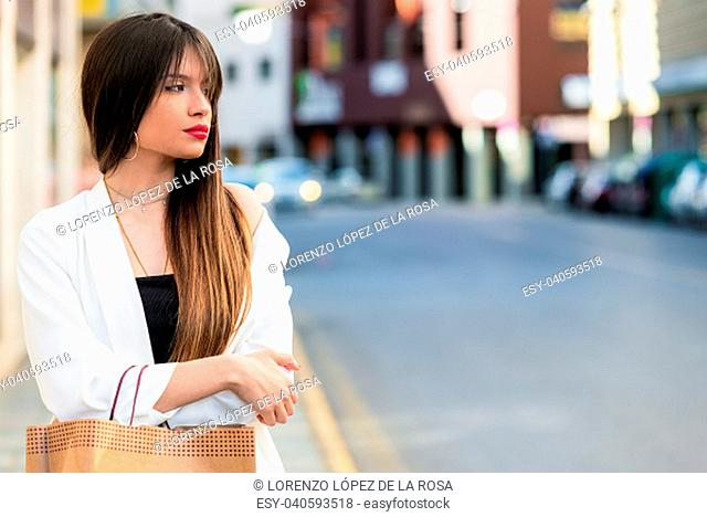 Beautiful young woman waiting in the street with copy space for text