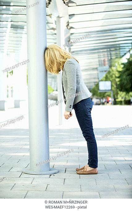 Frustated woman leaning against column