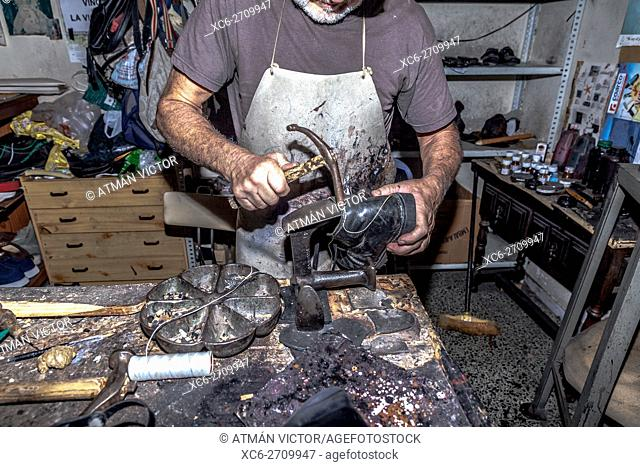 adult male shoemender working at his own workshop