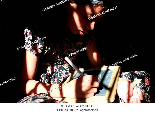 A girl writes at BRAC school Demra, Dhaka, Bangladesh January 2011