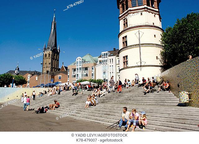 Germany, North Rhine Westphalia, Dusseldorf. People sitting on the stairs by the castle tower at the Rheinuferpromenade along the Rhine river