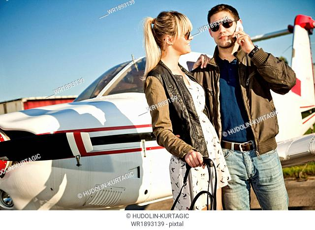 Young couple standing by airplane, man using phone