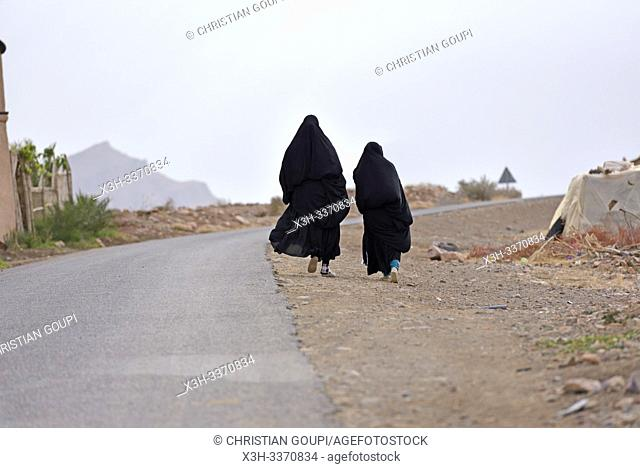 women dressed in black abaya walking along the road, Draa River valley, Province of Zagora, Region Draa-Tafilalet, Morocco, North West Africa