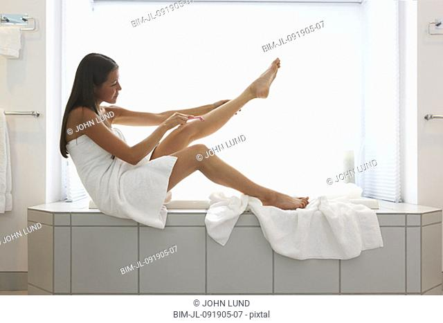 Woman wrapped in towel shaving legs on side of tub