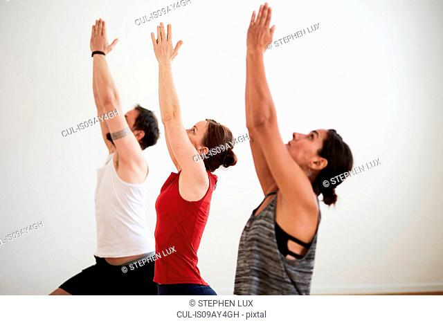 People in exercise studio arms raised in yoga position