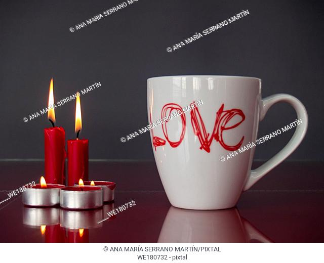 Concept of love Still life with red lit candles and a breakfast cup with the word love