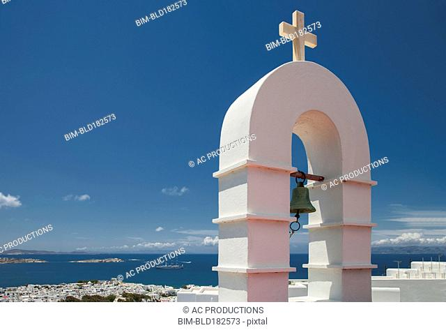 Bell arch and Mykonos cityscape under blue sky, Cyclades, Greece