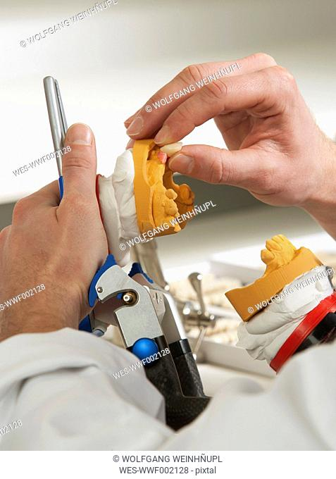 Dentist preparing dentures in dental laboratory