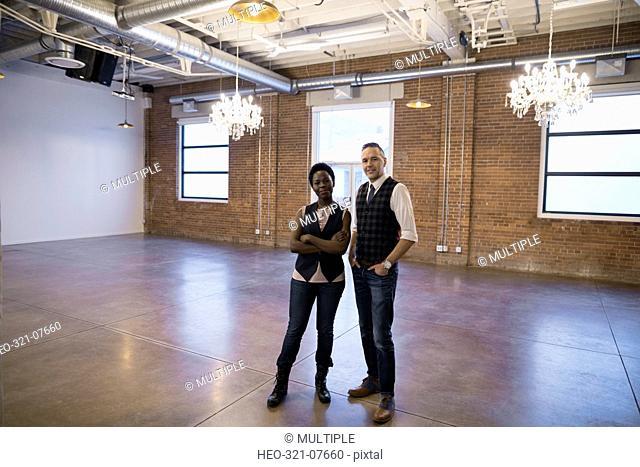 Portrait confident businessman and businesswoman in empty event space