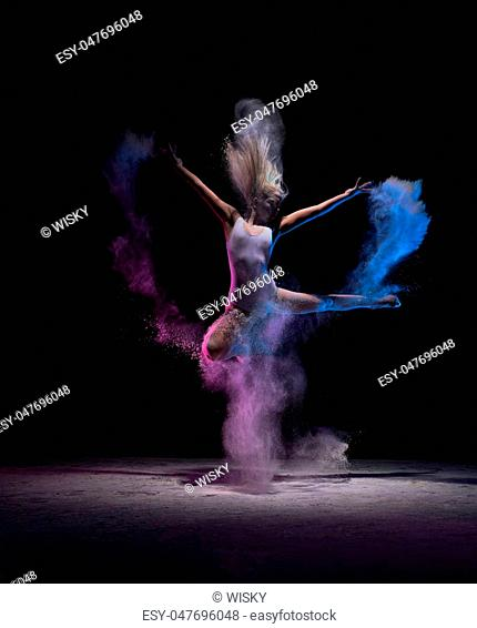 Contemporary art concept - young athletic dancer in motion at dark studio in cloud of powder or dry paints