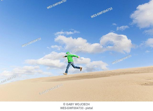 Man running down a sand dune