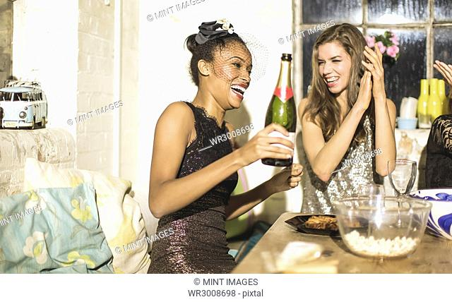 Two young women at a party in sequined dresses drinking and laughing, one holding a champagne bottle