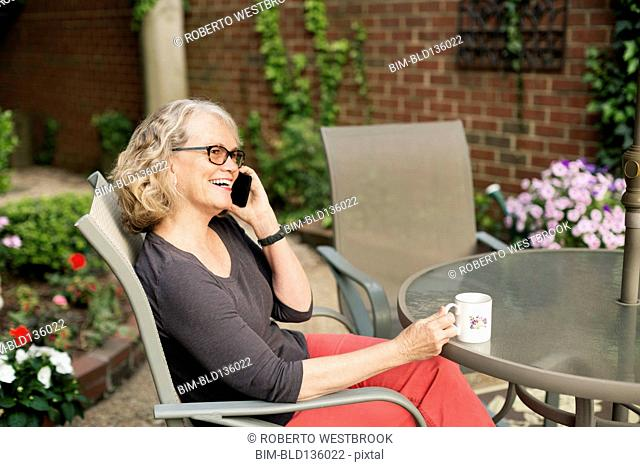 Caucasian woman talking on cell phone outdoors
