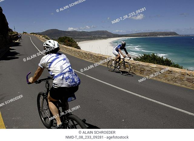 Two people riding bicycles near a beach, Noordhoek Beach, Cape Town, Western Cape Province, South Africa