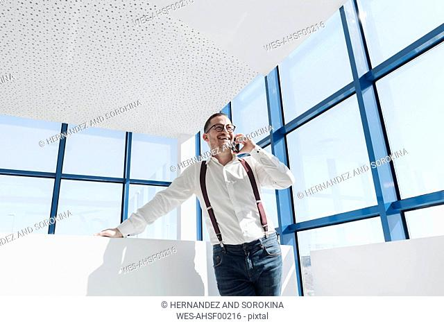 Happy businessman talking on cell phone at the window in modern office