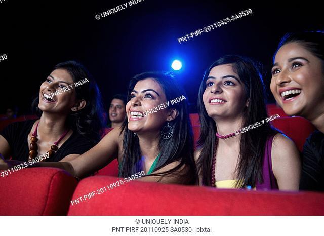 Female friends enjoying movie with popcorns in a cinema hall
