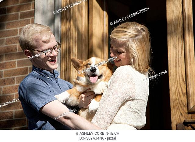 Happy young couple with corgi dog in arms outside front door
