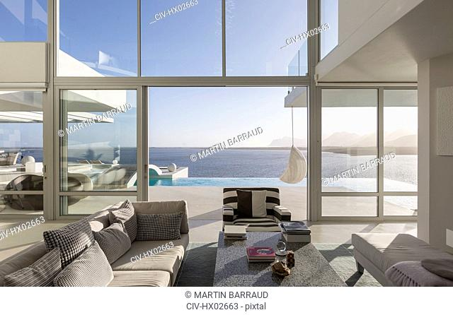 Sunny, tranquil modern luxury home showcase interior living room with patio and ocean view