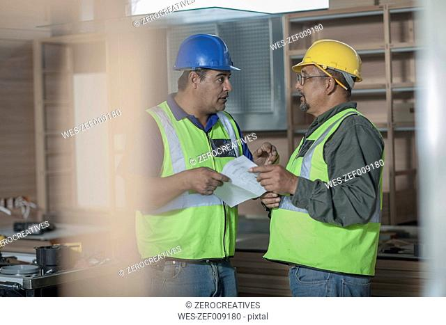 Two construction workers talking