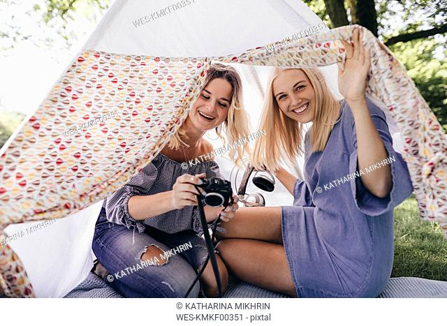 Two happy young women with old-fashioned camera in a teepee in a park