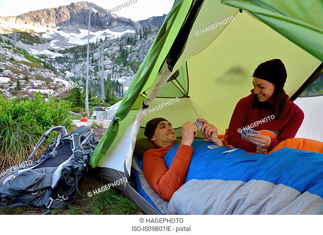 Couple playing card game in tent at Fault Lake, Selkirk Mountains, Idaho