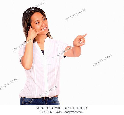 Portrait of an asiatic young woman saying call me while is looking and pointing to her left against white background - copyspace