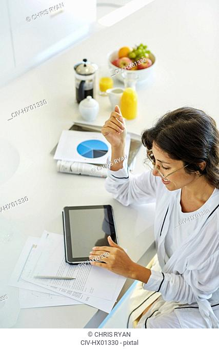 Woman in bathrobe working at digital tablet at kitchen counter