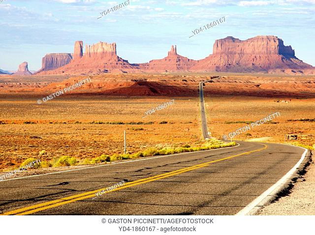 One of the most famous images of the Monument Valley is the long straight road US 163leading across flat desert towards sandstone buttes and pinnacles rock...