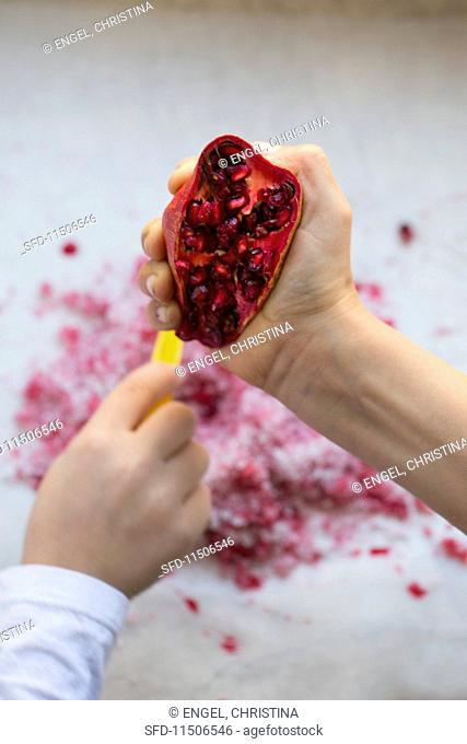 A child's hand squashing a pomegranate