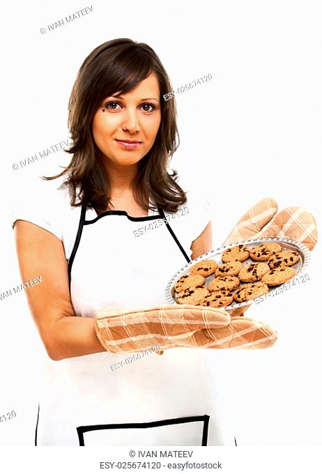 Young woman holding a tray with homemade chocolate cookies, looking at camera