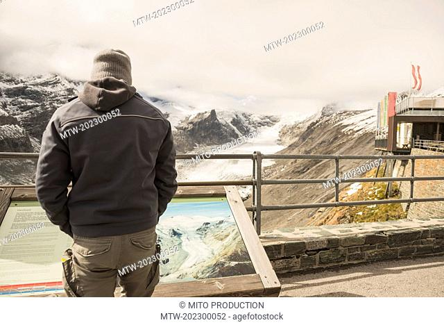 Mature man comparing the melting Grossglockner glacier and stream with a former image in a display cabinet, Glacier Pasterze, Hohe Tauern National Park