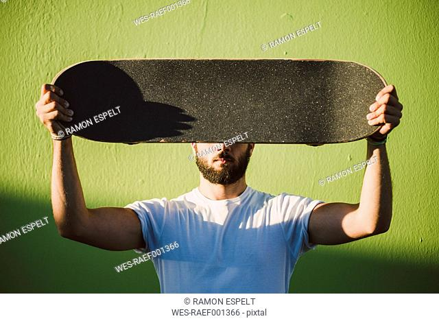 Man holding on his skateboard in front of his face