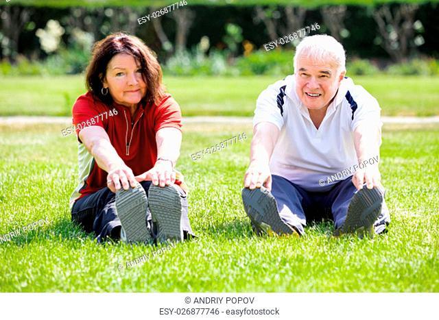 Elderly Senior Couple Doing Stretching Exercise In Park